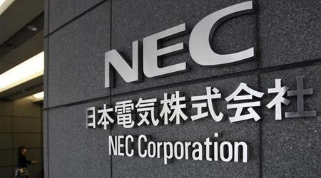A woman enters the NEC Corp headquarters building in Tokyo