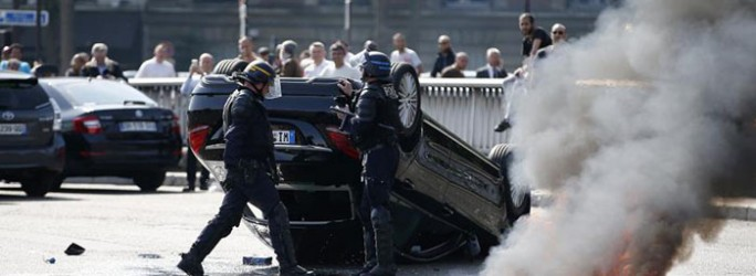 French riot police stand next to an overturned car as striking French taxi drivers demonstrate at Porte Maillot to block the traffic on the Paris ring road during a national protest against car-sharing service Uber, in Paris